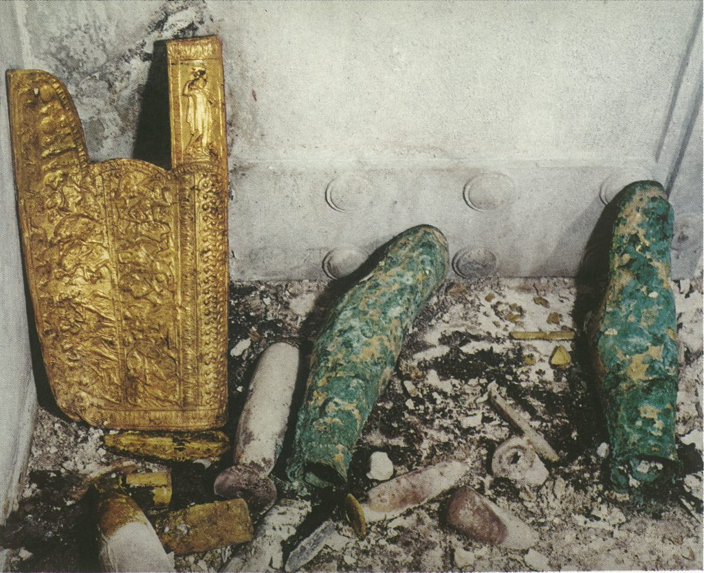 The gold quiver and greaves of the female in Tomb II stacked against the chamber-dividing door.